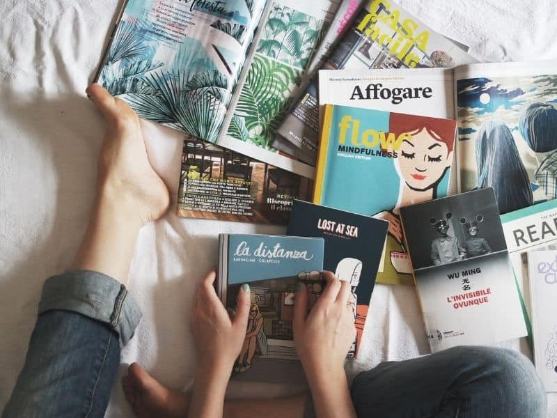 books spread out on a surface with woman's hands