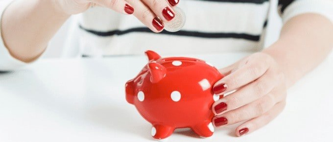 woman putting coins into red piggy bank