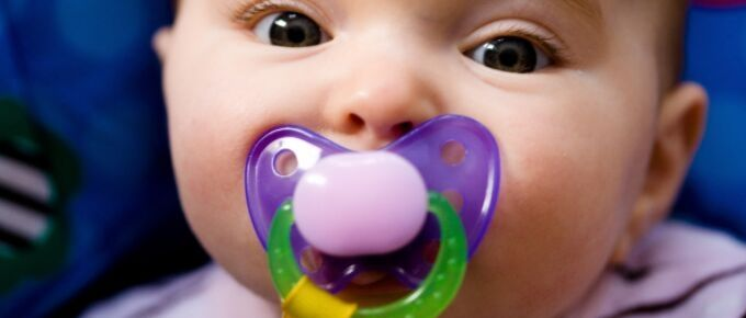 baby sucking pink and purple pacifier