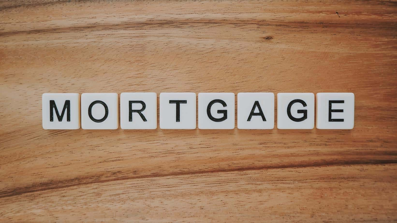 scrabble pieces spelling mortgage on a background