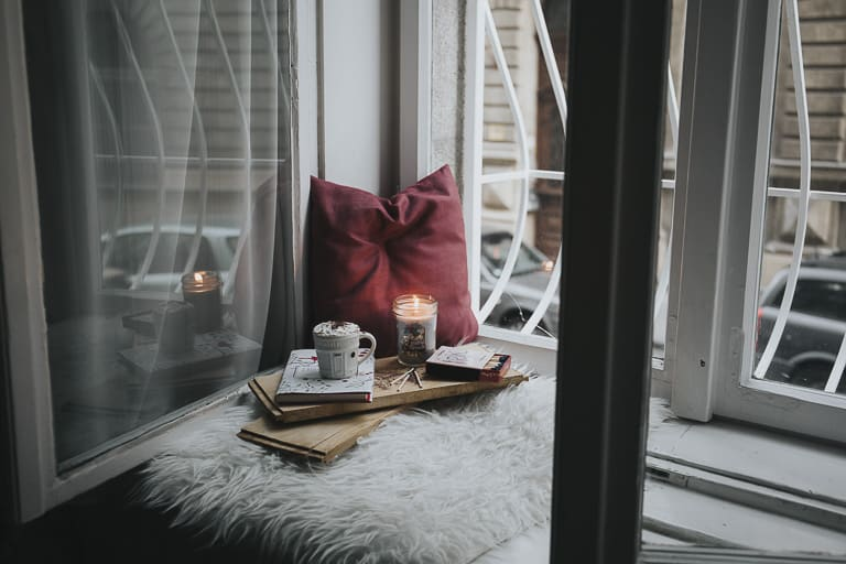 window seat with cushions, a cup of coffee and candles