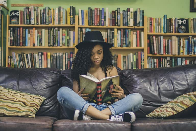 a girl sitting on a couch reading a book
