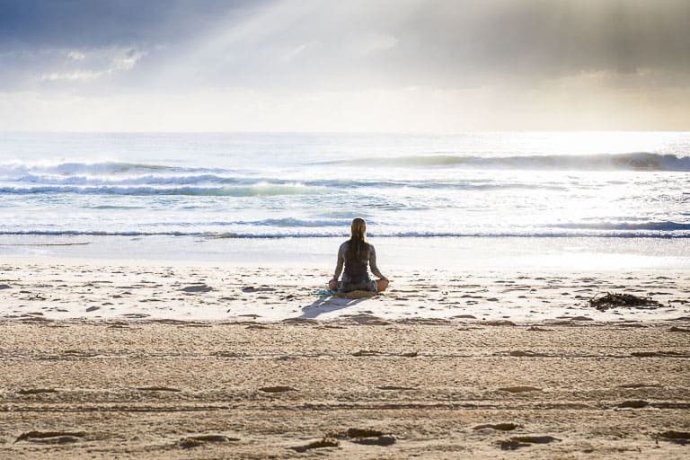 a woman sitting on the beach meditating
