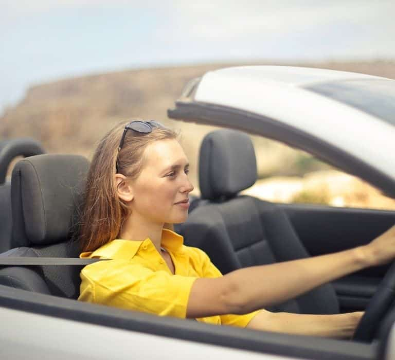 woman in a yellow shirt driving a car