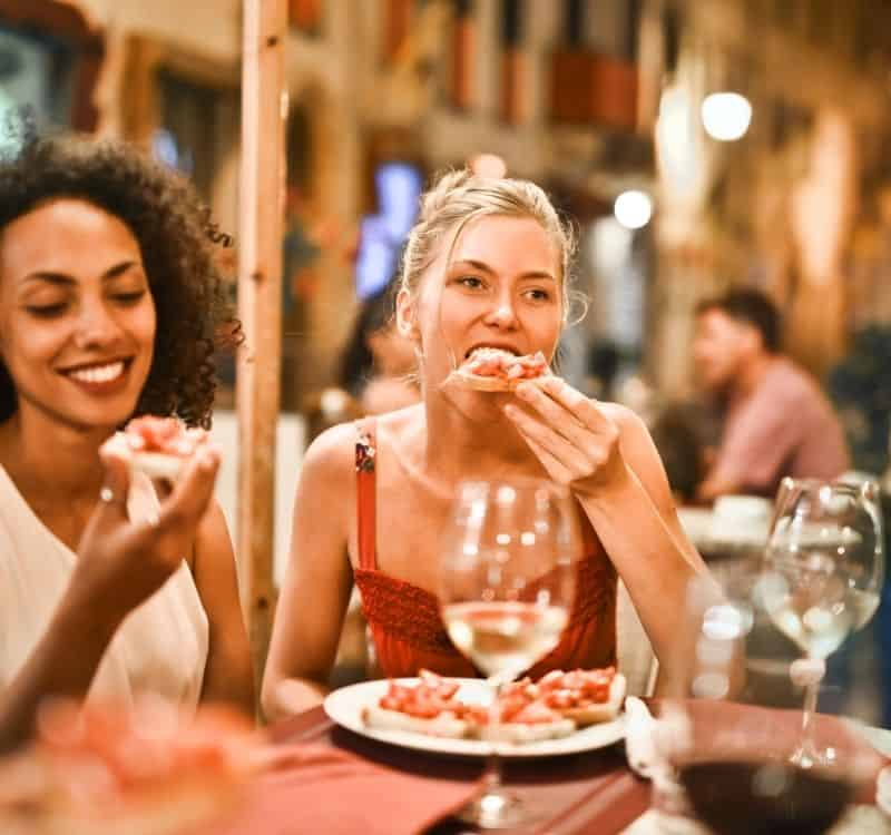 women eating pizza and drinking wine