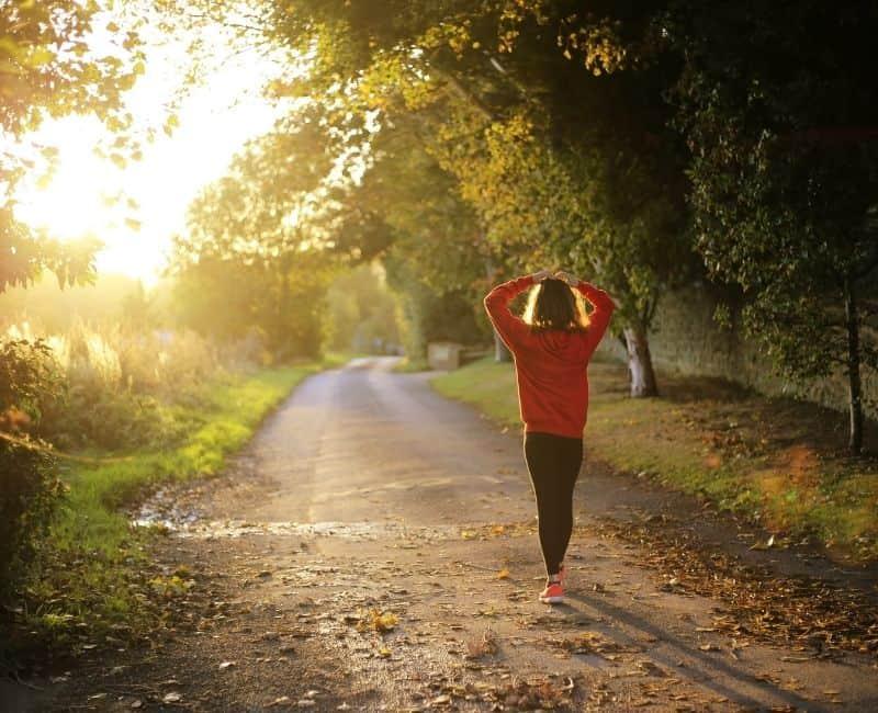 woman walking on a dirt road between trees