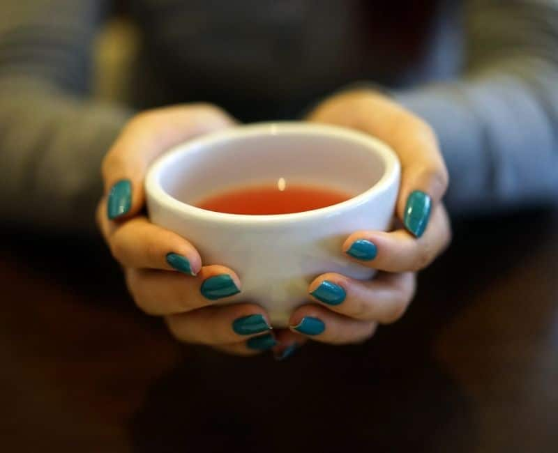 a pair of hands holding a cup of tea