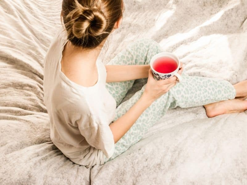 woman sitting on a bed holding a cup of tea