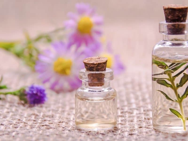 essential oils in bottles with flowers in the background