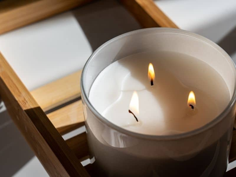 A CANDLE WITH 3 WICKS BURNING