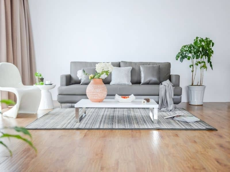 a couch in a living room with 2 chairs and a coffee table