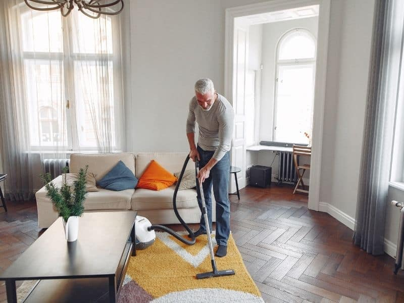 a man vacuuming a carpet in a living room
