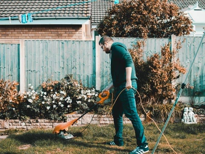 man using a weedwacker in the backyard