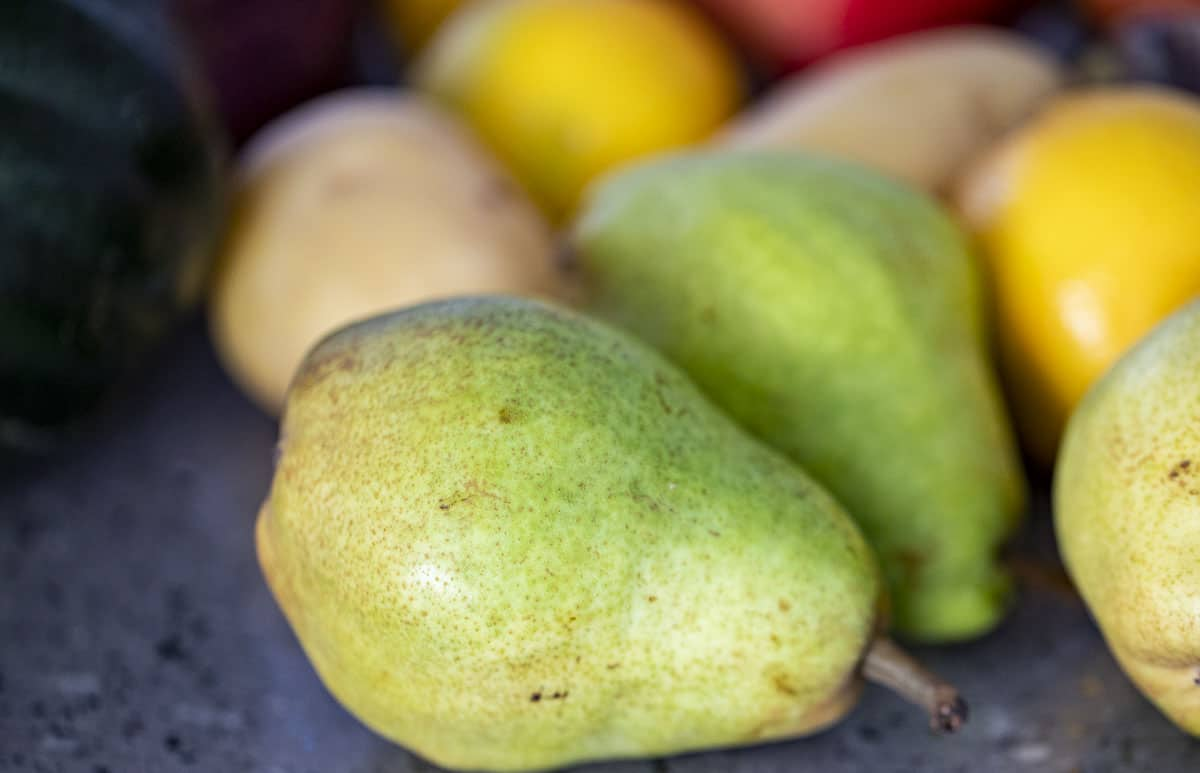 close up of a pear with other fruit behind it