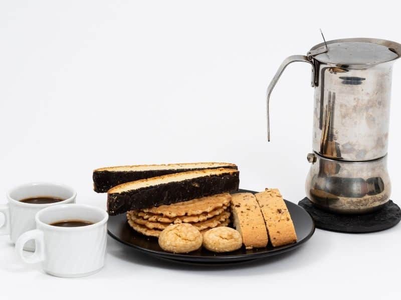 a plate of biscotti with 2 cups of coffee and a carafe on the side