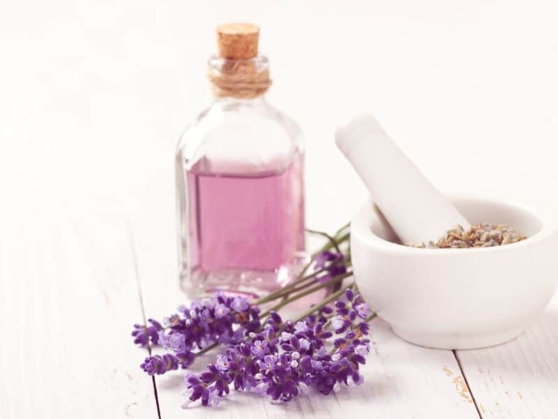 a bottle of pink liquid, lavender and a mortar and pestle