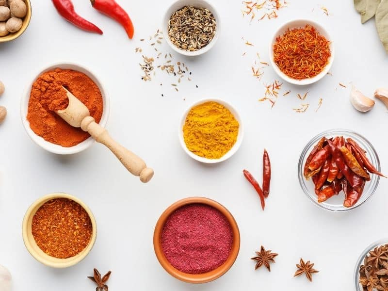 bowls of different spices on a white background
