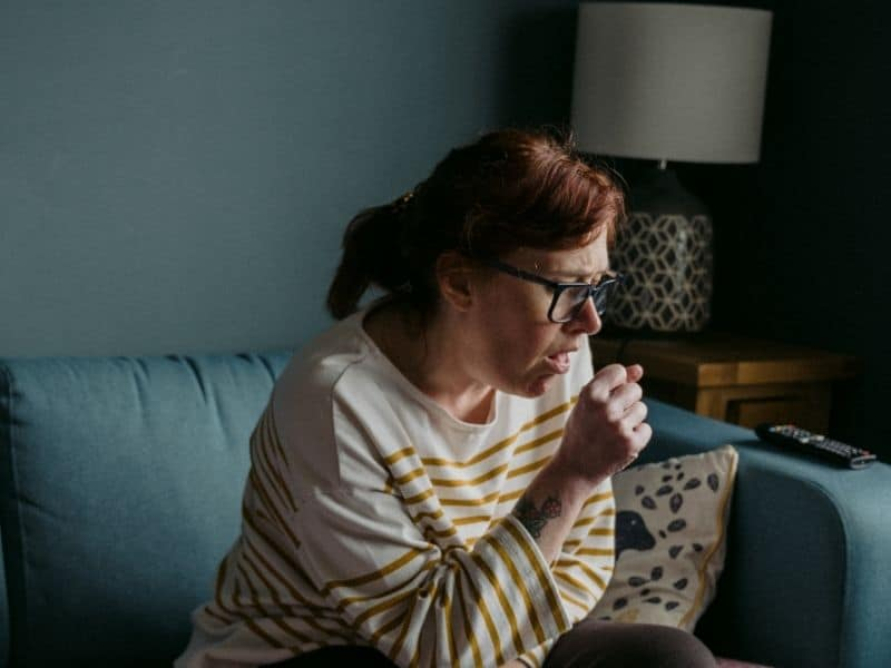 a woman sitting on a couch coughing