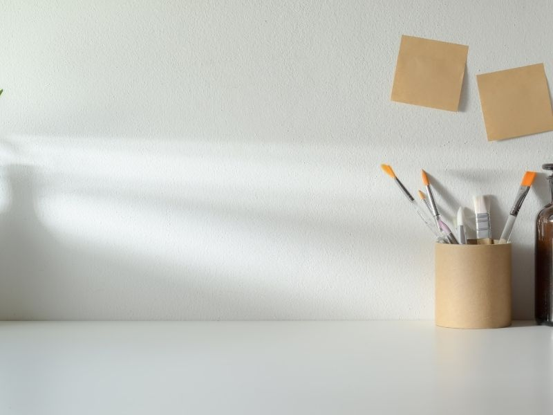a white table with a can of paintbrushes against a white wall