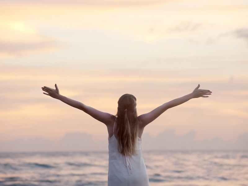 a woman looking at the ocean with her arms spread out