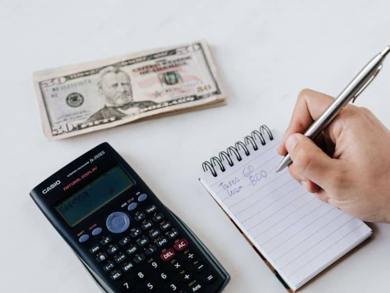 writing on a notepad with money and a calculator on the table
