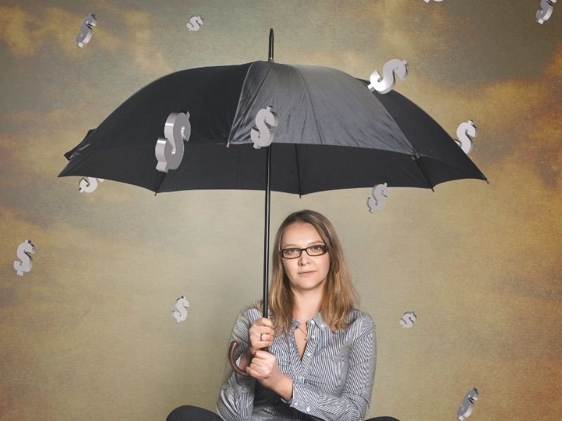 a woman holding an unbrella with dollar signs raining down