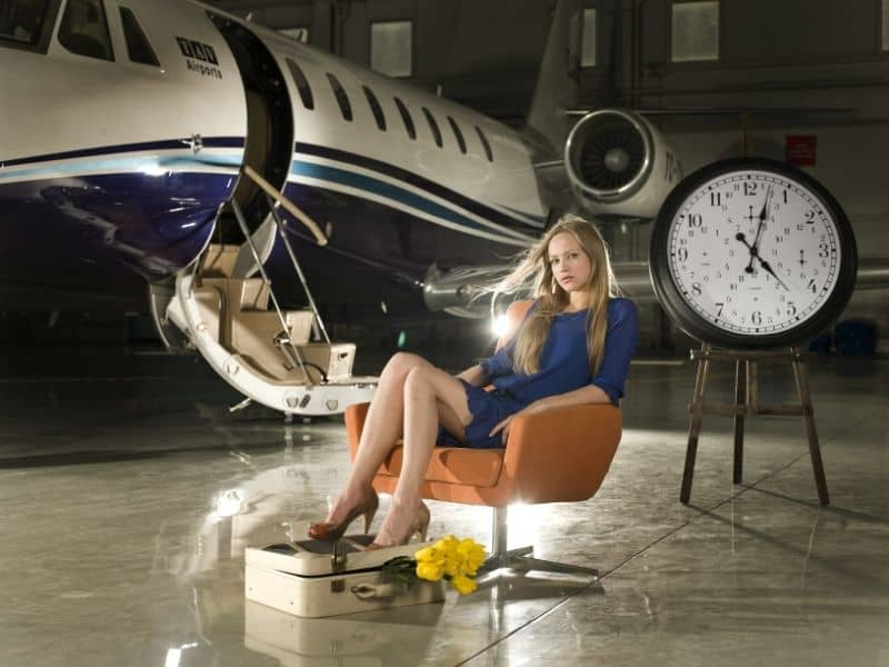 a woman sitting in a chair with a private jet in the background