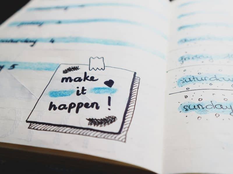 """a notebooks with""""make it happen"""" written in marjer"""