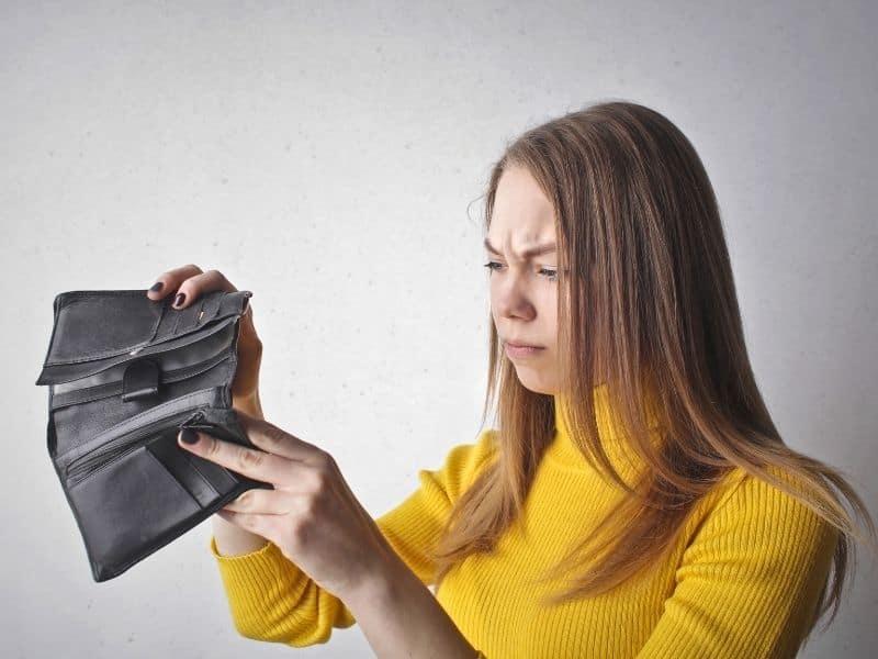 a woman looking inside an empty wallet