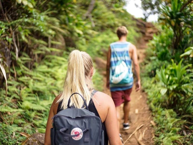 a couple hiking in the woods with backpacks on
