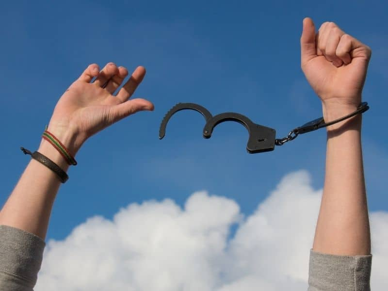 hands breaking free of handcuffs in the air