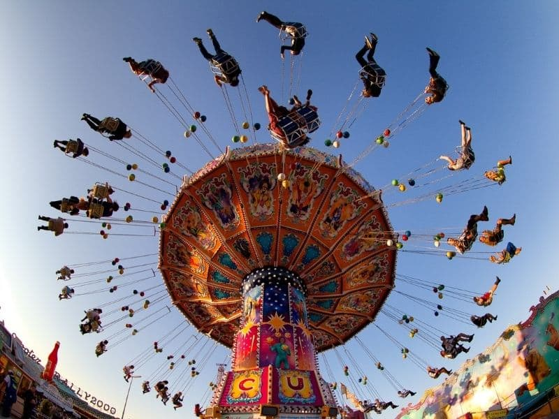 a carnical ride with chairs spinning in the air - colorful