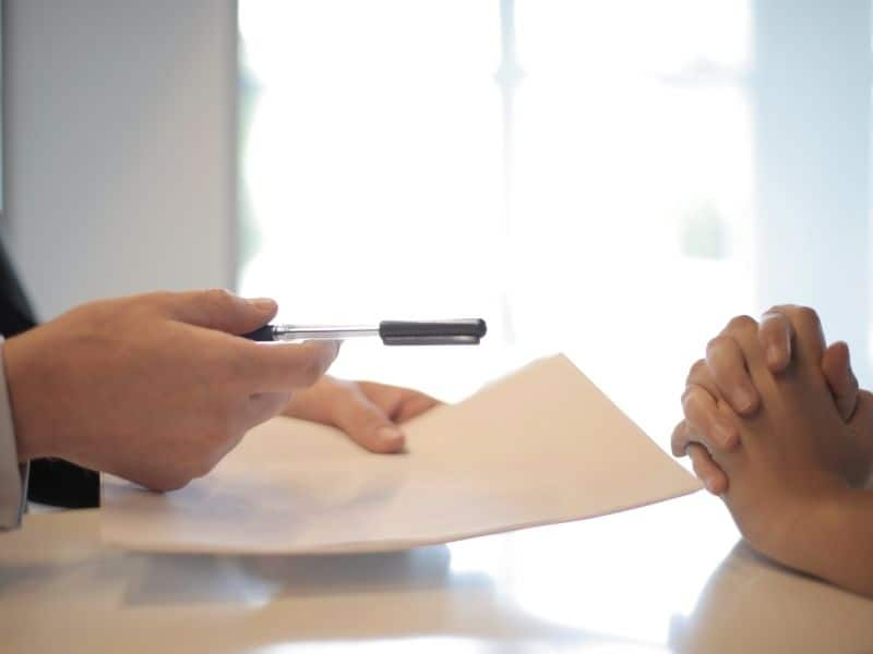 hands handing a pen and paper to another person