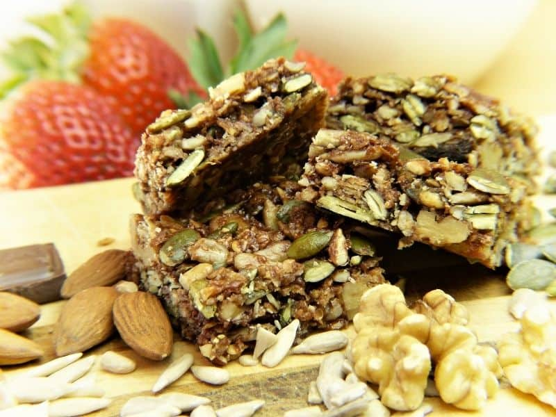 granola bars stacked with fruit in the background