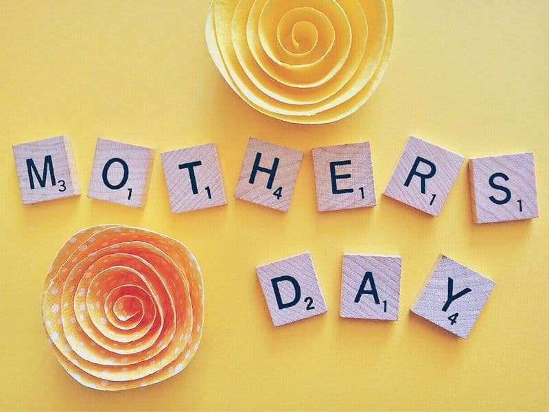 scrabble pieces spelling out mother's day on a yellow background