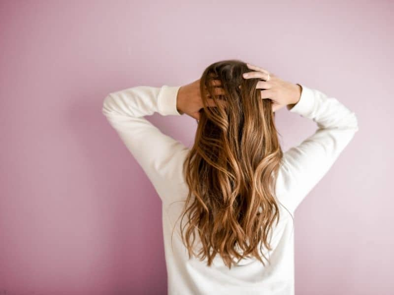 a woman with her back facing the camera and hands in her hair