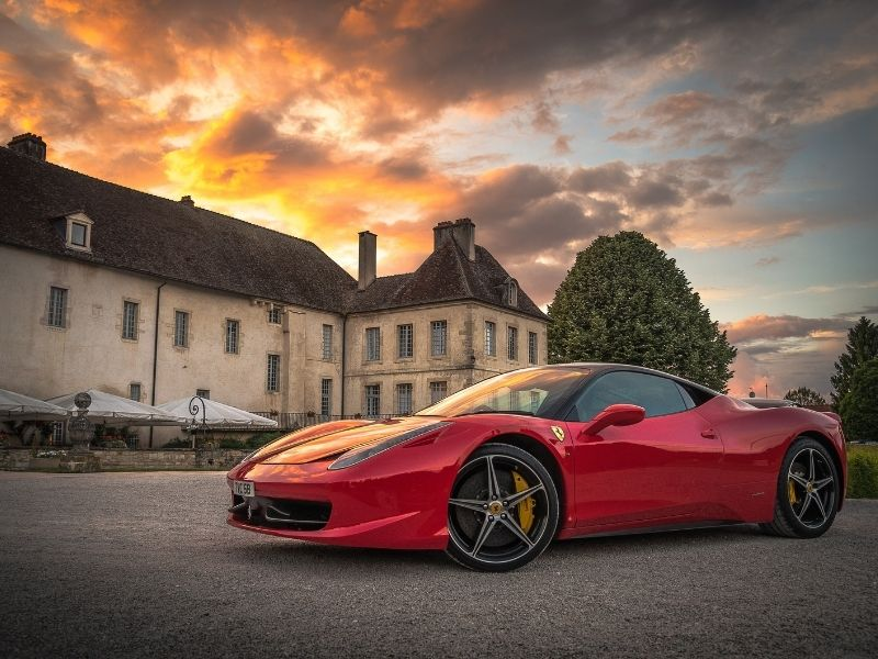 a red Ferrari in front of a mansion