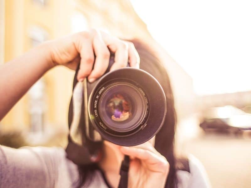 WOMAN HOLDING A CAMERA LENS POINTING AT THE CAMERA