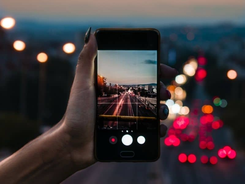 a hand holding a smartphone taking a photo of a busy road