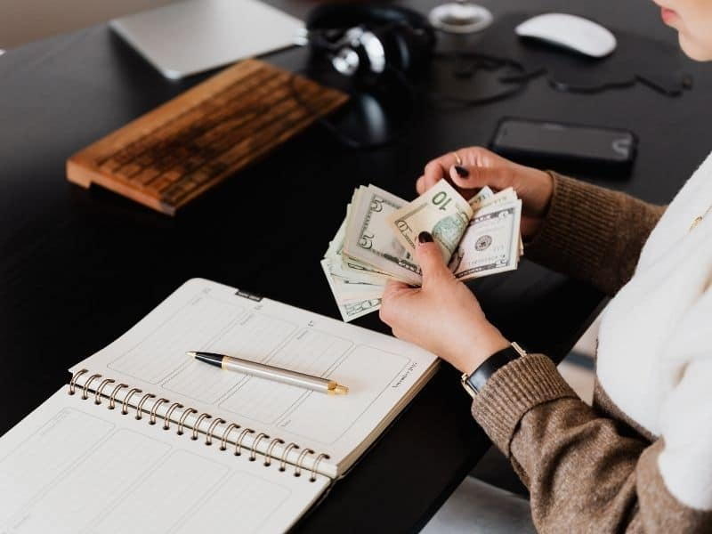 a woman counting money over a desk with a notepad