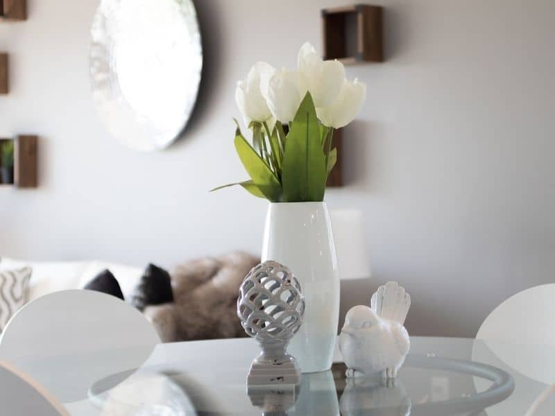 a vase and decor sitting on a table in a living room