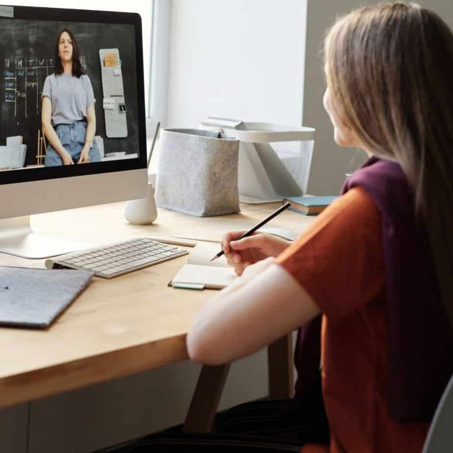 a woman sitting in front of a computer watching a video
