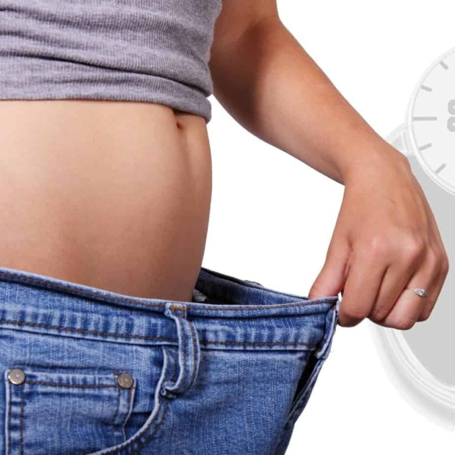 a woman holding her jeans out showing weight loss