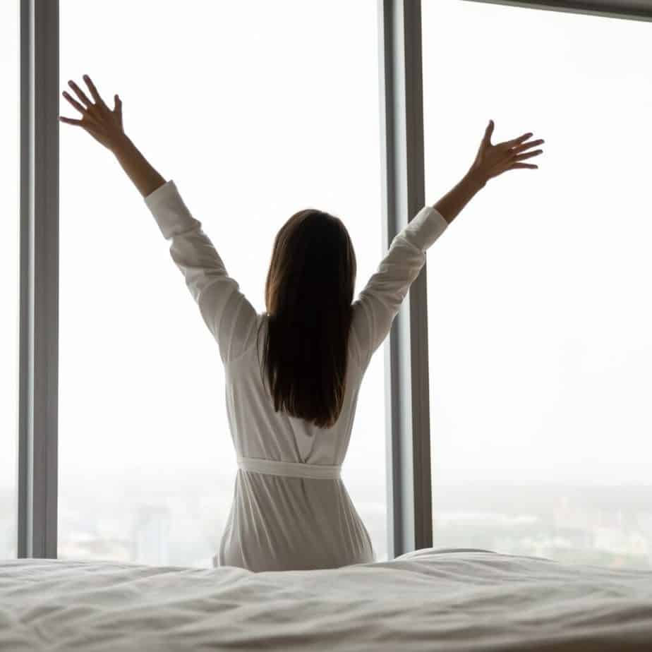 a woman in white waking up and stretching her arms in front of a window