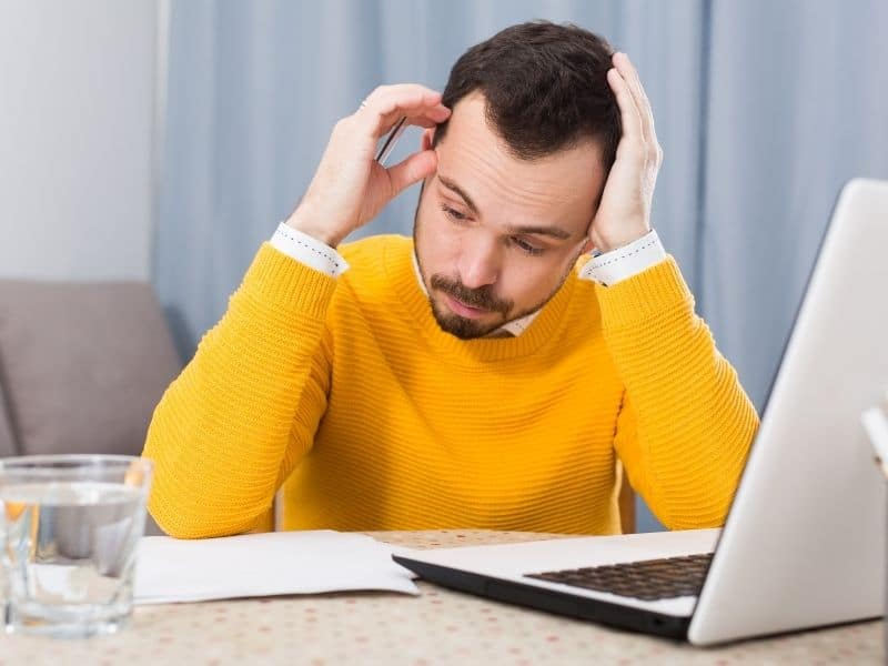 a man in a yellow sweater in front of a laptop