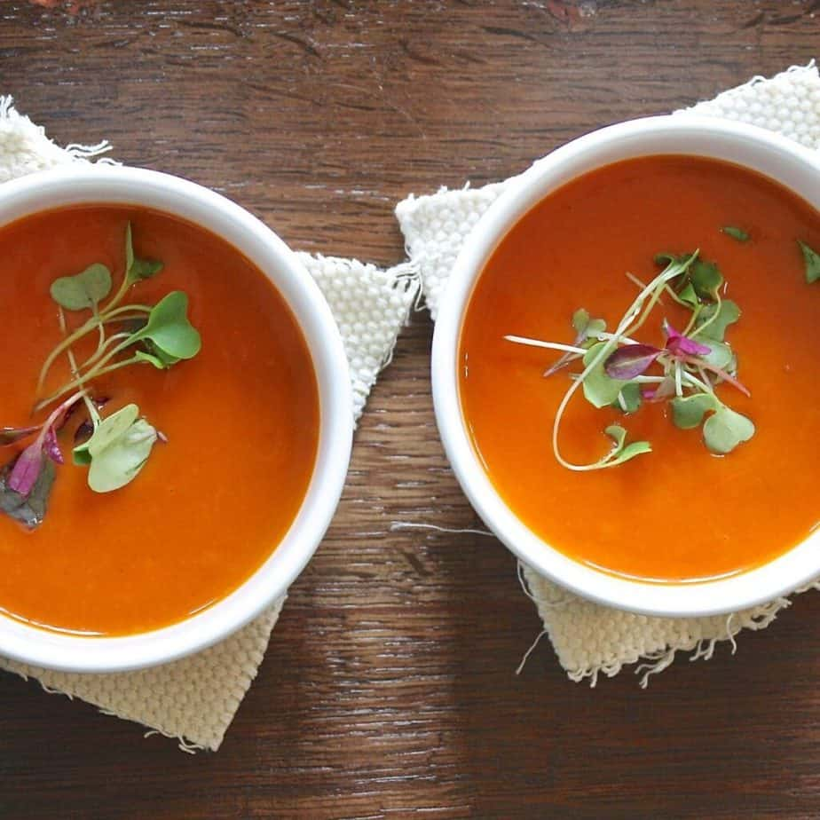 2 bowls of red tomato soup garnished with microgreens