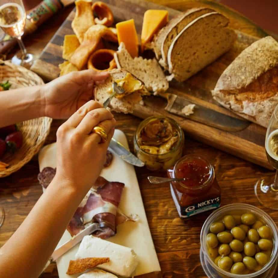 hands spreading sauce on bread over a charcuteries board