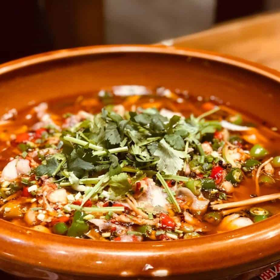 a bowl of chili garnished with cilantro and chilies
