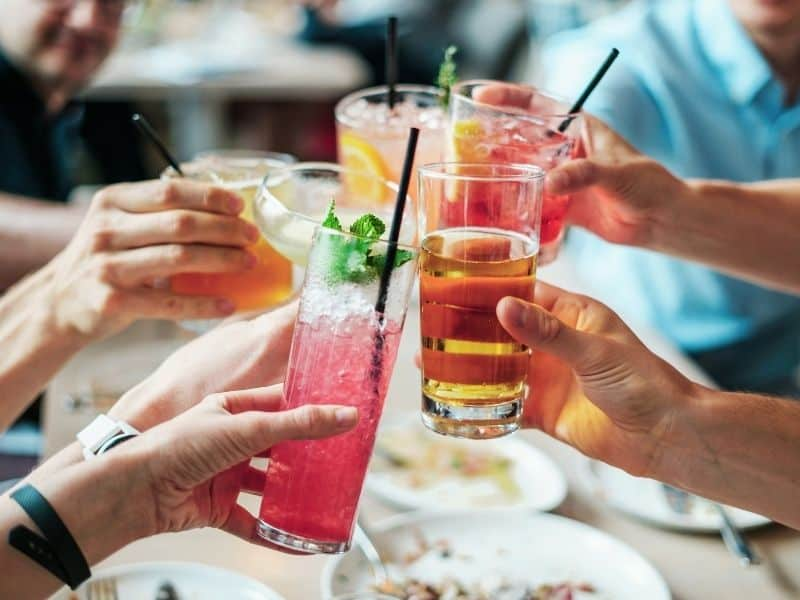 """hands holding cocktails doing a """"cheers"""""""