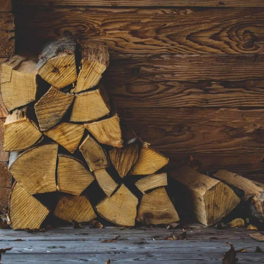 stack of firewood on pavement against a wood wall